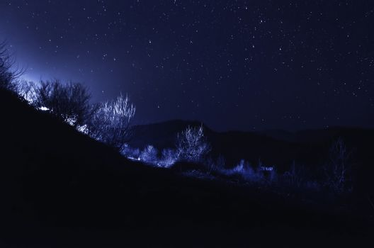 Beautiful stars on night sky over the mountains