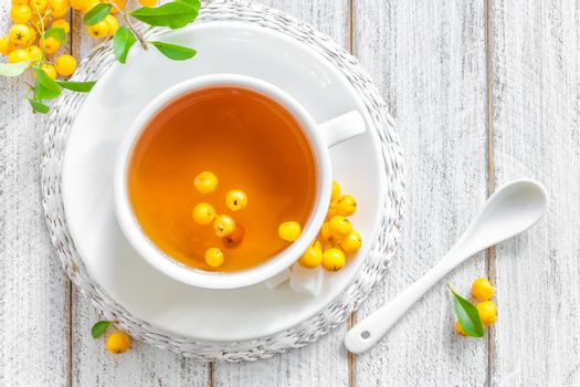 Fresh warmer herbal hawthorn tea with fresh berries in a white cup on wooden background, alternative medicine