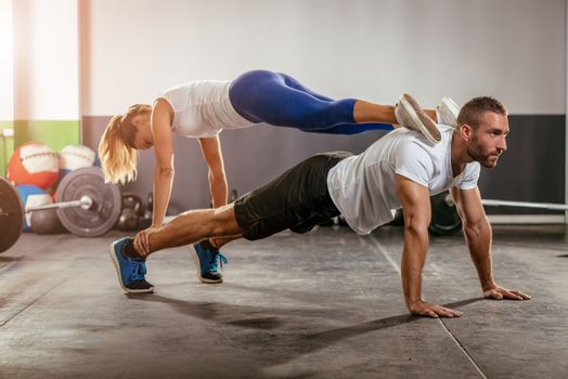 Young muscular man doing push-up exercise and holding girl above.