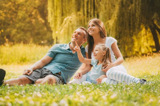 Happy smiling family sitting on the grass in the park and looking up.