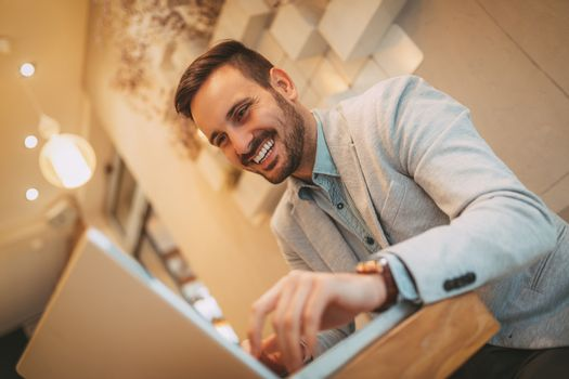 Young smiling businessman on a break in a cafe. He is working at laptop.