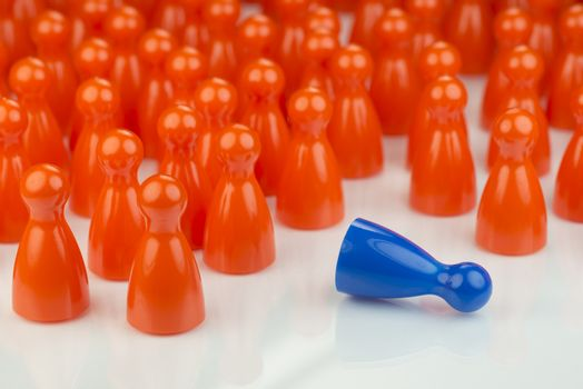 Conceptual orange game pawns and a blue play pawn as abstract display of inequality in color and number of