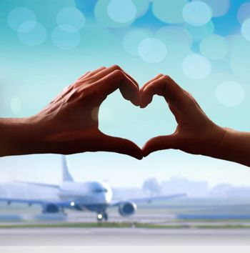 Silhouette of hands in form of heart when sweethearts have touched at airport