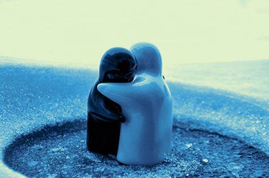 Love melts the ice Valentine `s day concept. F girl and a boy dolls hugs each other, standing on the white snow with blurred background. Hugging sculptures. Souvenir. Marble object. Love. Sympathy