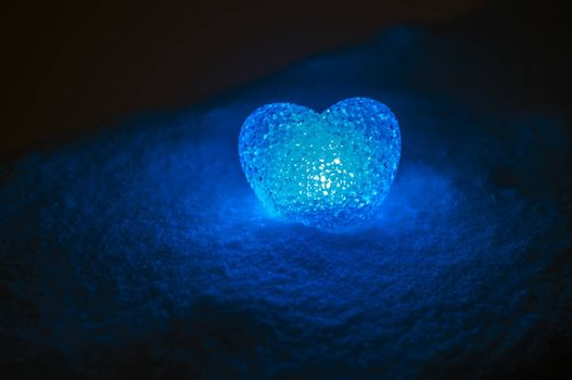 abstract glass heart on snow at night. Card for a Valentine's day. blue heart llight on black background