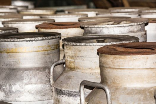 Old milk cans in a row on a farm