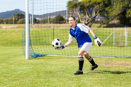 Female goalkeeper about to throw a football