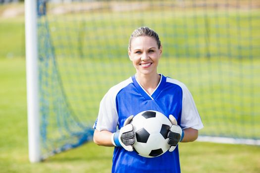 Female goalkeeper standing with ball