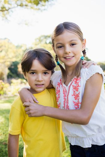 Portrait of brother and sister arm in arm