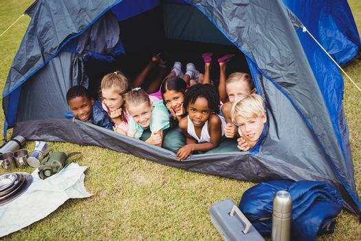 Smiling kids lying in the tent together