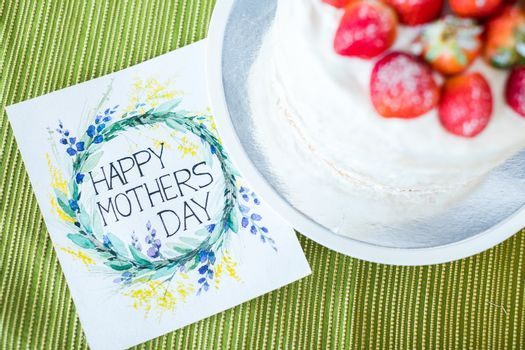 Top view of beautiful Mothers Day greeting card and cake with strawberries