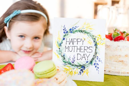 Close-up view of happy mothers day greeting card with pastries and little girl smiling at camera