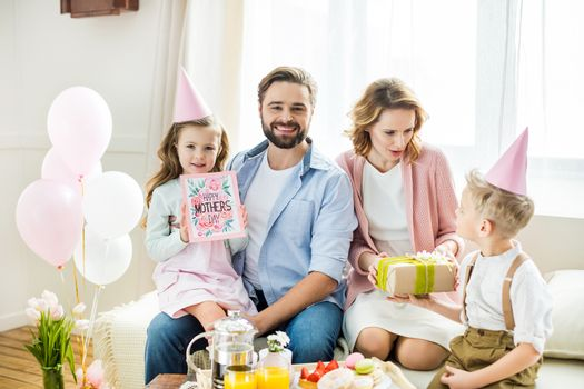 Happy family sitting at festive table with present and greeting card for Mothers day