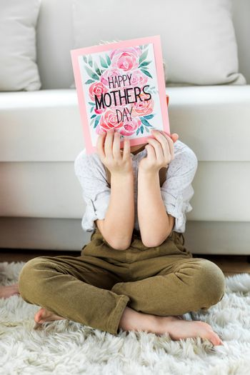 Little boy sitting on carpet and hiding face with happy mothers day greeting card