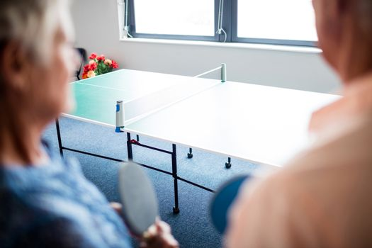 Two seniors front of a ping pong table