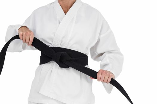Female athlete tightening her judo belt