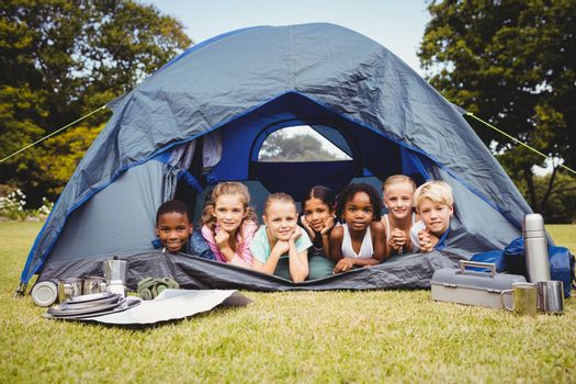 Smiling children lying in the tent together