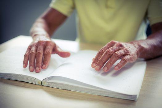 Senior blind man reading a braille book