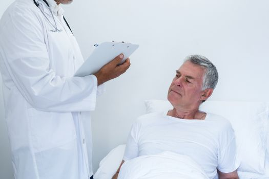 Male doctor writing medical report of senior man on clipboard