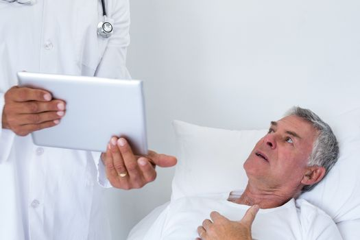 Male doctor discussing medical reports with senior man on digital tablet
