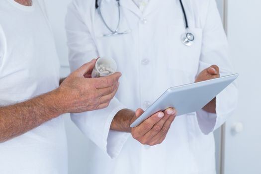 Male doctor showing medical reports to senior man on digital tablet