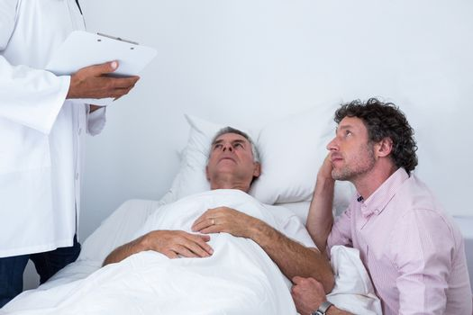 Man sitting next to patients bed and listening to the doctor