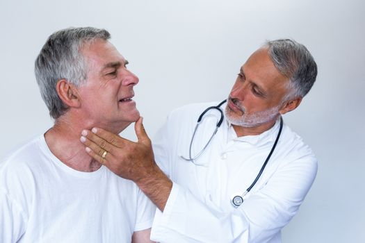 Male doctor examining senior mans neck
