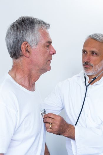 Male doctor checking heartbeat of senior man