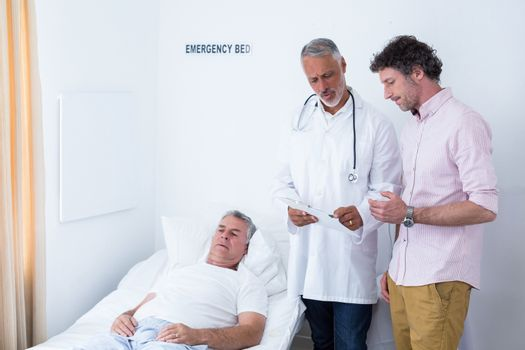 Male doctor discussing medical report with man