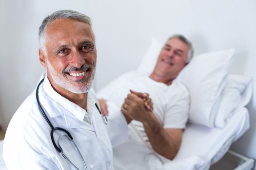 Male doctor consoling senior man