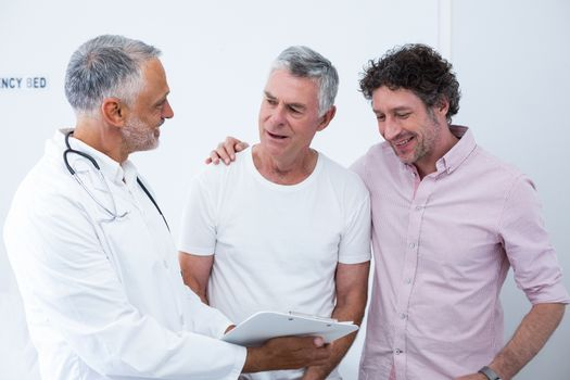 Senior man and his guardian talking to the doctor