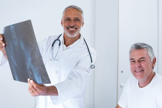 Male doctor discussing x-ray with senior man