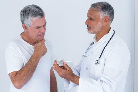Male doctor advising senior man on medical prescriptions