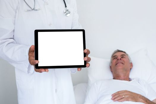 Doctor standing next to the patient and holding a digital tablet