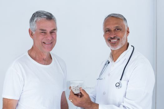 Portrait of male doctor giving pills to senior man