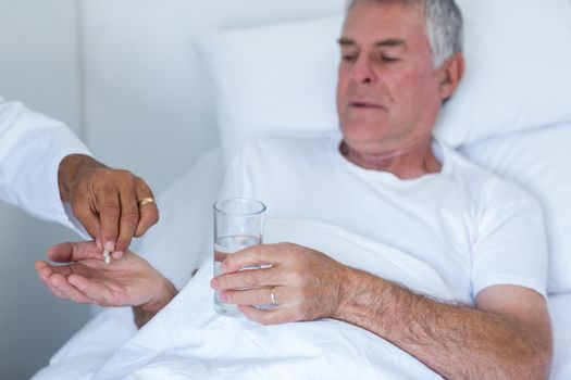 Male doctor giving pill to senior man
