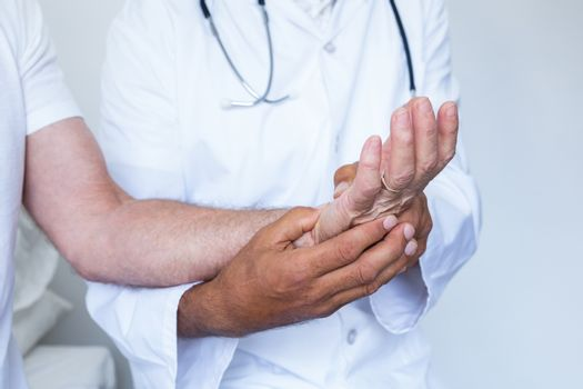 Male doctor giving palm acupressure treatment to the patient