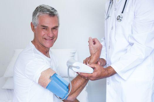 Doctor checking senior mans blood pressure