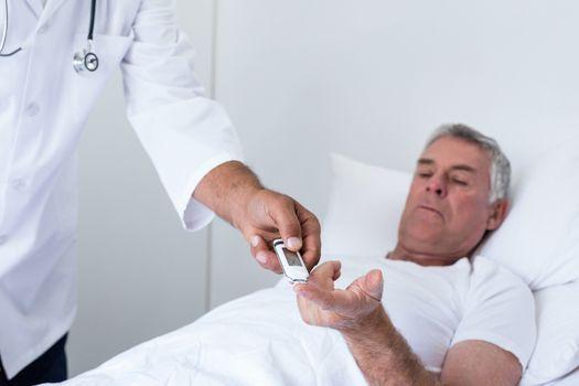Male doctor testing diabetes of senior man on glucose meter