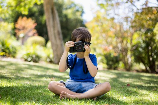 Young boy clicking a photograph from camera