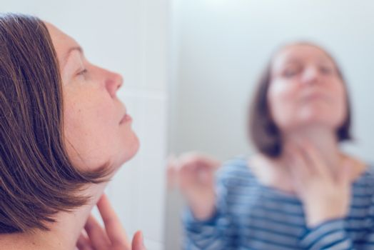 Young adult woman applying anti-aging cream