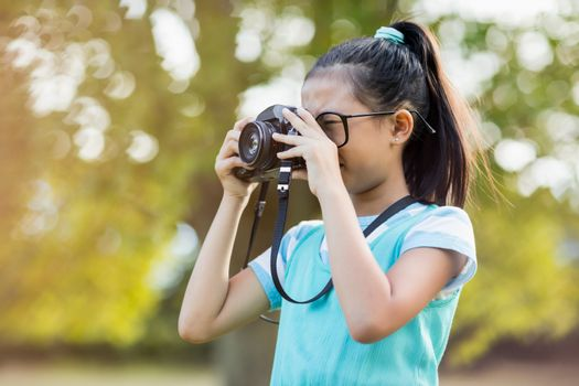 Young girl clicking a photograph from camera