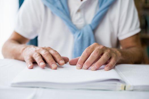 Senior man using braille to read