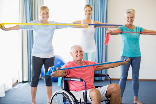 Instructor and seniors exercising with stretching bands