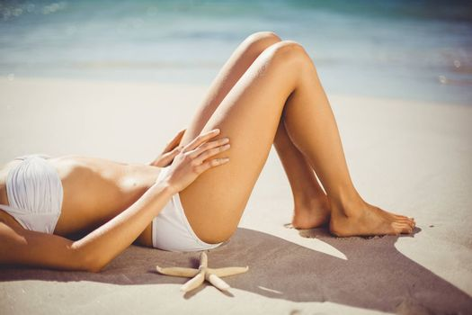 Attractive woman lying alone on sand