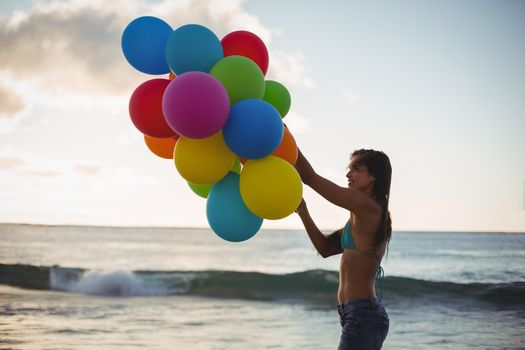 Woman holding colorful balloon