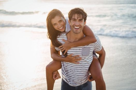 Man giving woman piggyback ride on the beach