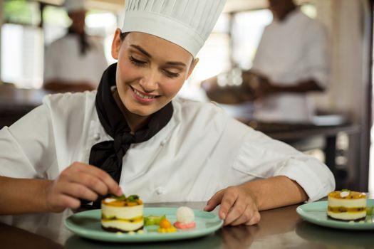 Female chef finishing dessert plates