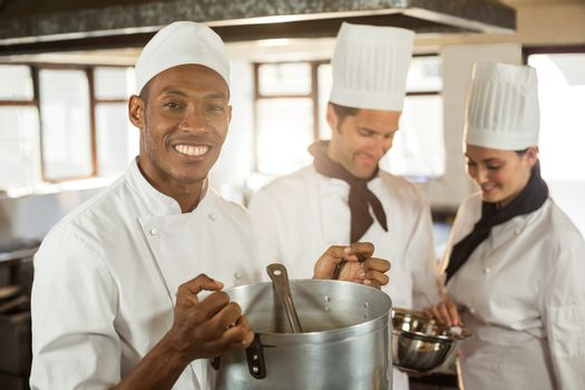 Portrait of smiling chef holding a cooking pot in commercial kitchen