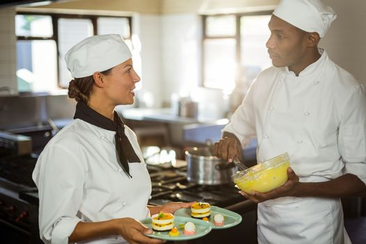 Chefs talking to each other while working in kitchen